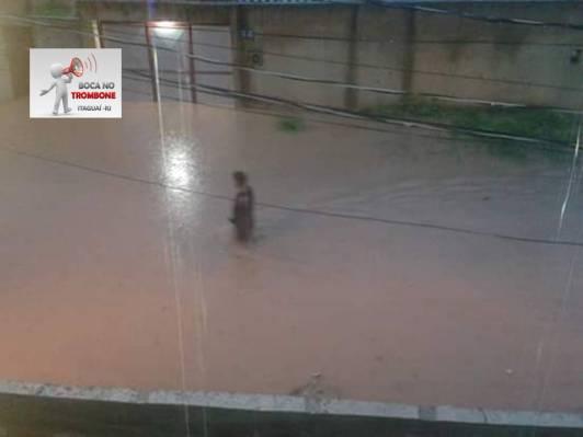Um homem tenta atravessar a rua alagada para chegar em casa após o trabalho